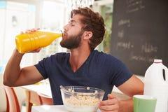 Νεαρός άνδρας που τρώει το πρόγευμα και που πίνει το χυμό από πορτοκάλι Στοκ φωτογραφία με δικαίωμα ελεύθερης χρήσης
