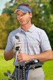 Νεαρός άνδρας που υπερασπίζεται το σύνολο τσαντών γκολφ των ραβδιών Στοκ φωτογραφίες με δικαίωμα ελεύθερης χρήσης