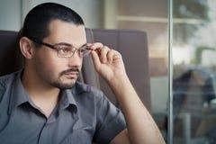 Νεαρός άνδρας που φορά τα γυαλιά που κοιτάζουν από ένα παράθυρο Στοκ Εικόνα