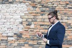 Νεαρός άνδρας που φορά τα γυαλιά που χρησιμοποιούν τον υπολογιστή ταμπλετών έξω Στοκ εικόνα με δικαίωμα ελεύθερης χρήσης