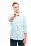 Νεαρός άνδρας που χαμογελά και που δείχνει στη κάμερα πέρα από το άσπρο υπόβαθρο Στοκ Εικόνες