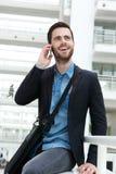 Νεαρός άνδρας που χαμογελά με το κινητό τηλέφωνο Στοκ Φωτογραφίες