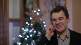 Νεαρός άνδρας που χαμογελά μιλώντας στο τηλέφωνο απόθεμα βίντεο
