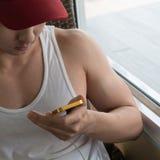 Νεαρός άνδρας που χρησιμοποιεί ένα κινητό τηλέφωνο με το μήνυμα Στοκ Εικόνες