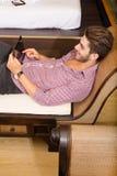 Νεαρός άνδρας που χρησιμοποιεί ένα PC ταμπλετών σε ένα ασιατικό δωμάτιο ξενοδοχείου Στοκ Φωτογραφία