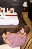 Νεαρός άνδρας που χρησιμοποιεί ένα PC ταμπλετών σε ένα ασιατικό δωμάτιο ξενοδοχείου Στοκ φωτογραφία με δικαίωμα ελεύθερης χρήσης