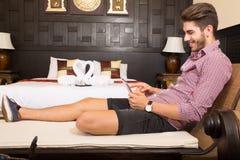 Νεαρός άνδρας που χρησιμοποιεί ένα PC ταμπλετών σε ένα ασιατικό δωμάτιο ξενοδοχείου Στοκ Εικόνες