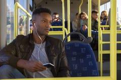 Νεαρός άνδρας που χρησιμοποιεί ένα smartphone στο λεωφορείο στοκ εικόνες