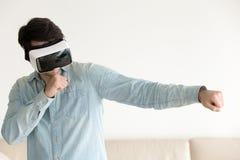 Νεαρός άνδρας που χρησιμοποιεί την κάσκα VR, παίζοντας το παιχνίδι εικονικής πραγματικότητας, εγκιβωτισμός Στοκ εικόνα με δικαίωμα ελεύθερης χρήσης