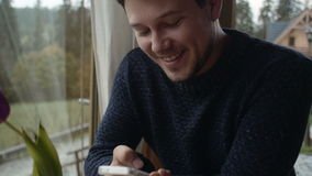 Νεαρός άνδρας που χρησιμοποιεί τη συνεδρίαση smartphone στο καθιστικό φιλμ μικρού μήκους
