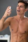 Νεαρός άνδρας που χρησιμοποιεί τον ψεκασμό αναπνοής μεντών στοκ εικόνα