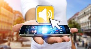 Νεαρός άνδρας που χρησιμοποιεί το σύγχρονο κινητό τηλέφωνο για να ακούσει μουσική Στοκ Εικόνες