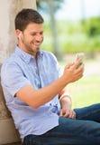 Νεαρός άνδρας που χρησιμοποιεί το τηλέφωνο κυττάρων Στοκ εικόνες με δικαίωμα ελεύθερης χρήσης
