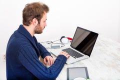 Νεαρός άνδρας που χρησιμοποιεί το φορητό προσωπικό υπολογιστή του στο σπίτι Στοκ φωτογραφίες με δικαίωμα ελεύθερης χρήσης