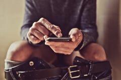 Νεαρός άνδρας που χρησιμοποιεί το smartphone του στην τουαλέτα Στοκ Εικόνες