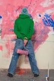 Νεαρός άνδρας που χρωματίζει έναν τοίχο Στοκ εικόνες με δικαίωμα ελεύθερης χρήσης