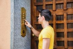 Νεαρός άνδρας που χτυπά doorbell και που μιλά στον ομιλητή στοκ εικόνα