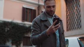Νεαρός άνδρας που sms, χρησιμοποιώντας app στο smarphone στην πόλη Όμορφος επιχειρηματίας που χρησιμοποιεί την τεχνολογία οθονών  φιλμ μικρού μήκους