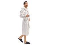 Νεαρός άνδρας σε ένα μπουρνούζι που κρατά ένα φλυτζάνι και ένα περπάτημα Στοκ Εικόνες