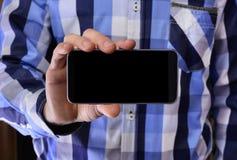 Νεαρός άνδρας σε ένα μπλε πουκάμισο καρό που κρατά ένα τηλέφωνο με το μαύρο s Στοκ φωτογραφία με δικαίωμα ελεύθερης χρήσης
