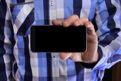 Νεαρός άνδρας σε ένα μπλε πουκάμισο καρό που κρατά ένα τηλέφωνο με το μαύρο s Στοκ Φωτογραφίες