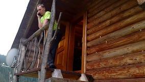 Νεαρός άνδρας σε ένα ξύλινο πεζούλι που μιλά στο τηλέφωνο απόθεμα βίντεο