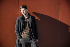 Νεαρός άνδρας σε μια χειμερινή εξάρτηση που κλίνει στον κόκκινο τοίχο Στοκ Εικόνες