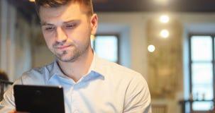 Νεαρός άνδρας/σπουδαστής που χρησιμοποιεί τον υπολογιστή ταμπλετών όμορφο σε σοβαρό καφέδων φιλμ μικρού μήκους