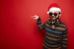 Νεαρός άνδρας στα γυαλιά ηλίου και καπέλο Santa που δείχνει μακριά Στοκ φωτογραφίες με δικαίωμα ελεύθερης χρήσης