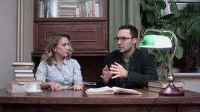 Νεαρός άνδρας στα γυαλιά και γυναίκα σπουδαστής που εργάζεται μαζί στο ερευνητικό πρόγραμμα φιλμ μικρού μήκους
