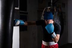 Νεαρός άνδρας στα εγκιβωτίζοντας γάντια που εκπαιδεύει με τον εγκιβωτισμό punching της τσάντας Στοκ φωτογραφία με δικαίωμα ελεύθερης χρήσης