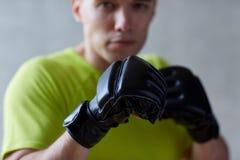 Νεαρός άνδρας στα εγκιβωτίζοντας γάντια στο εσωτερικό Στοκ εικόνα με δικαίωμα ελεύθερης χρήσης
