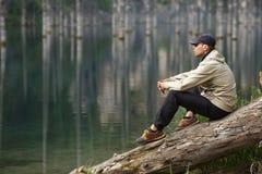 Νεαρός άνδρας στην ακτή μιας λίμνης βουνών Στοκ Εικόνα