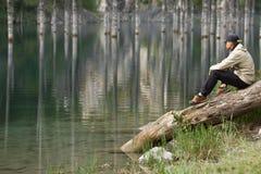 Νεαρός άνδρας στην ακτή μιας λίμνης βουνών Στοκ εικόνες με δικαίωμα ελεύθερης χρήσης