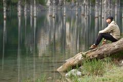 Νεαρός άνδρας στην ακτή μιας λίμνης βουνών Στοκ φωτογραφία με δικαίωμα ελεύθερης χρήσης
