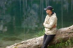 Νεαρός άνδρας στην ακτή μιας λίμνης βουνών Στοκ εικόνα με δικαίωμα ελεύθερης χρήσης