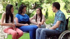 Νεαρός άνδρας στην αναπηρική καρέκλα με την οικογένεια στο πάρκο απόθεμα βίντεο