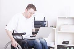 Νεαρός άνδρας στην αναπηρική καρέκλα στο σπίτι γραφείο στοκ φωτογραφίες με δικαίωμα ελεύθερης χρήσης