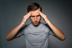 Νεαρός άνδρας στην μπλούζα που σκέφτεται ή που δοκιμάζει τους πονοκέφαλους Στοκ φωτογραφία με δικαίωμα ελεύθερης χρήσης
