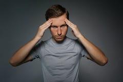 Νεαρός άνδρας στην μπλούζα που σκέφτεται ή που δοκιμάζει τους πονοκέφαλους Στοκ Εικόνες