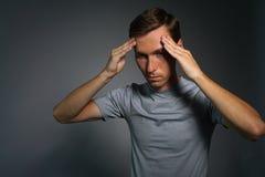 Νεαρός άνδρας στην μπλούζα που σκέφτεται ή που δοκιμάζει τους πονοκέφαλους Στοκ Φωτογραφία