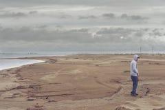 Νεαρός άνδρας στην παραλία που φορά ένα hoodie και ένα καπέλο του μπέιζμπολ Στοκ Εικόνες