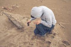 Νεαρός άνδρας στην παραλία που φορά ένα hoodie και ένα καπέλο του μπέιζμπολ Στοκ φωτογραφία με δικαίωμα ελεύθερης χρήσης