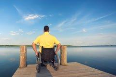 Νεαρός άνδρας στη λίμνη με την αναπηρική καρέκλα του στοκ εικόνες