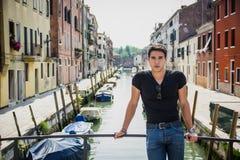 Νεαρός άνδρας στη γέφυρα πέρα από το στενό κανάλι στη Βενετία Στοκ Φωτογραφίες