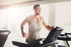 Νεαρός άνδρας στη γυμναστική που οργανώνεται treadmill Στοκ φωτογραφία με δικαίωμα ελεύθερης χρήσης