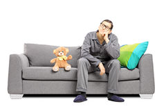Νεαρός άνδρας στις πυτζάμες στις σκέψεις που κάθονται στον καναπέ με τη teddy αρκούδα Στοκ Εικόνες