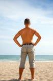 Νεαρός άνδρας στις στάσεις σορτς στην αμμώδη παραλία Στοκ εικόνα με δικαίωμα ελεύθερης χρήσης