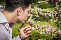 Νεαρός άνδρας στον κήπο που μυρίζει τα όμορφα λουλούδια Στοκ Εικόνα