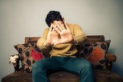 Νεαρός άνδρας στον καναπέ που καλύπτει το πρόσωπό του Στοκ Φωτογραφίες